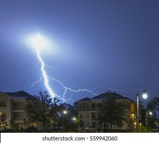 Massive blue lightning strikes in a neighborhood