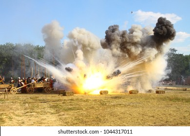 Massive bomb explosion during re-enactment of medieval battle. Blowing up on the battlefield with flame and clouds of  white and black smoke. Detonation of the cannon ball. Living history festival.