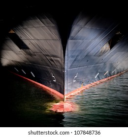 The massive bow of a large ship, with the radar dome cresting the surface of the water.