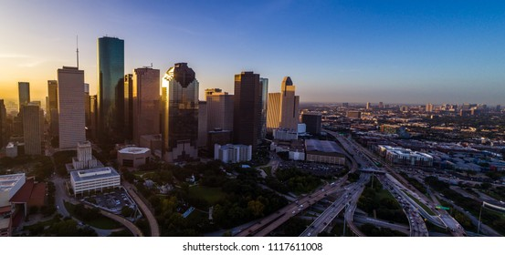 Massive city along gulf coast Houston Texas sunrise aerial drone view golden hour ring around horizon y'all skyscrapers downtown skyline cityscape with traffic and highways with a high flood risk