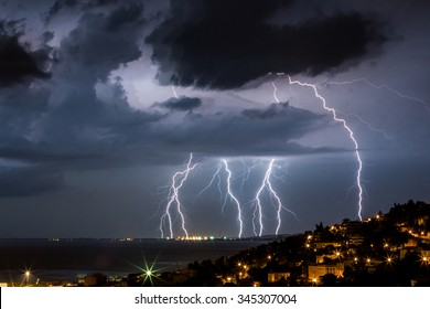 Massive cloud to ground lightning bolts hitting the horizon of city lights