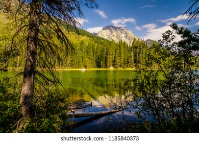 The massive Grand Teton peaks in the background are overlooking the Leigh Lake area of Grand Teton National Park in Wyoming. There are beautiful mountain, sky, and forest reflections in the lake.