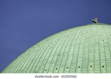 Massive green dome with a christian cross on top of Hedwig's Cathedral in Berlin Mitte.
