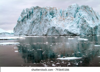 Massive Greenland iceberg reflected in the dark waters of the Arctic Ocean, off the west coast of Greenland. A colossal wall of ice above and below waterline and many times the size of the Titanic.