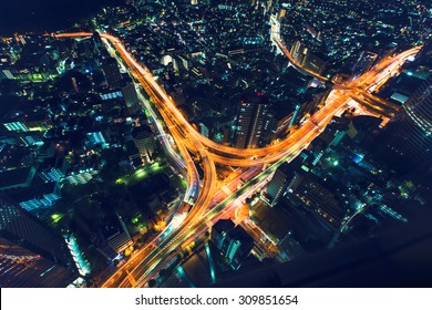 A massive highway intersection from above at night in Shinjuku, Tokyo, Japan