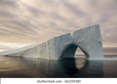 A massive iceberg sports a double arch, creating a passageway completely through the berg, in Baffin Bay, between Canada and Greenland.