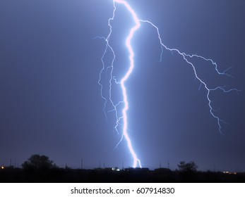 A massive lightning bolt striking behind a home in Arlington Arizona during the 2009 Monsoon season. This bolt struck less than 1000 feet from my location. Any closer and I might not have lived.