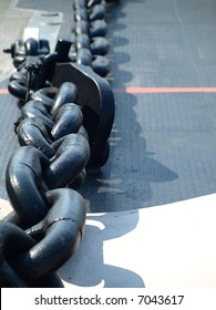 A massive metal chain on the deck of a naval ship (shallow DOF)