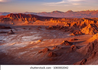 A massive moon crater with salt deposit in the middle of eerie terrain at the Valle de Luna, or Moon Valley, at San Pedro de Atacama. Sunset light casts shadow on mountains and changes its colours.