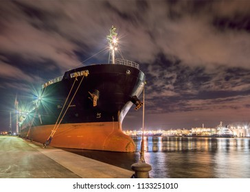 Massive moored oil tanker at night with a dramatic cloudy sky, Port of Antwerp, Belgium.
