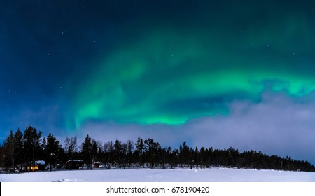 Massive Northern lights (aurora borealis) over the small cabin in the woods in Swedish Lapland.