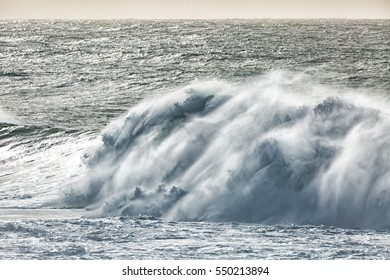 Massive pacific ocean wave breaks into the stormy surf. High shutter speed provides good detail of the wave-break action