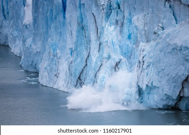 Massive piece of iceberg falling down into water