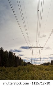 The massive power line pylons rise above the fields of the Northern Finland. The summer sky is slowly getting darker.