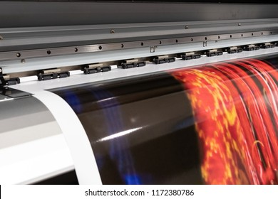 Massive print head processing an oversized glossy color sample before initiating customer orders.