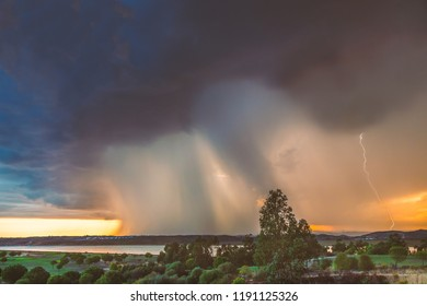 A massive rain cloud approaches as a storm rain breaks over Ayamonte, Andalusia Spain and the Guadiana river at sunset. The sky is golden behind the clouds and there is a lightning strike.