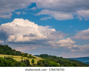 Massive rain clouds forming in the blue sky over hilly landscape