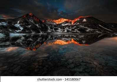 Massive Retezat mountains sunset reflection in crystal clear lake with rocks