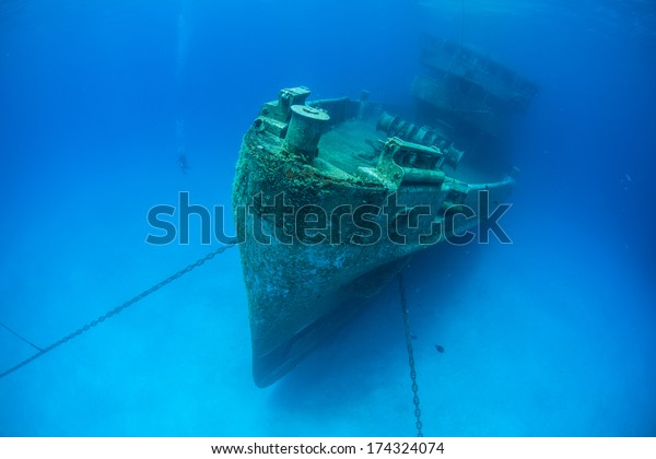 A massive shipwreck, the Kittewake, sits on a sandy seafloor in Grand Cayman. This ship was sunk intentionally to act as an artificial reef and as an attraction for scuba divers.