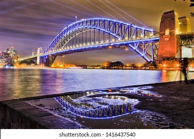 Massive steel arch of the Sydney harbour bridge over Sydney harbour reflecting in puddle with blue laser beams in dark sky at Vivid Sydney light show.