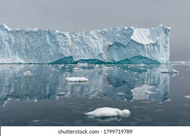 A massive tabular iceberg and its reflection in the calm glassy water in Antarctica.