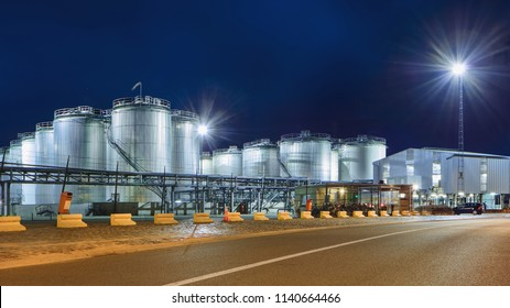 Massive tanks at illuminated petrochemical production plant at nighttime, Port of Antwerp, Belgium.