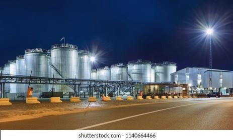 Massive Tanks in beleuchteter petrochemischer Produktionsanlage nachts, Hafen von Antwerpen, Belgien.