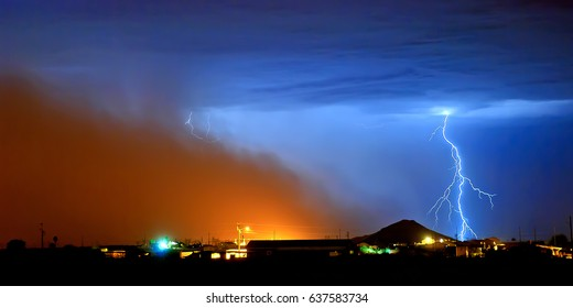 A massive wall of dust rolling into a rural area west of Phoenix Arizona. This storm came in at night and was only revealed when lightning flashed near it. These storms are also called Haboobs.