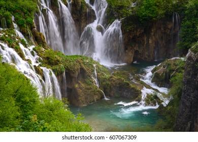 Massive waterfall among lush foliage. Scene in Plitvice Lakes National Park.