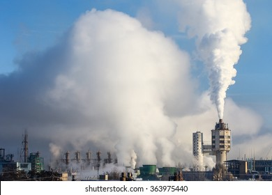 Massive white smokes coming out of factory chimney. Factory surrounded by smog. Air pollution. Industrial landscape