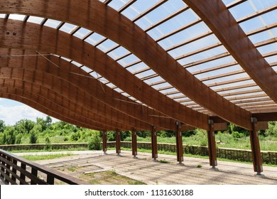 massive wood beams roof structure with S curved shaped and covered with transparent polycarbonate sheet