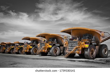 Massive yellow excavation trucks lined up. Used for transporting mine ore. Industrial transportation. Spot color yellow. All logos removed.