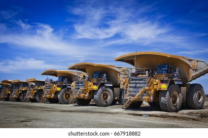 Massive yellow excavation trucks lined up. Used for transporting mine ore. Industrial transportation. All logos removed.