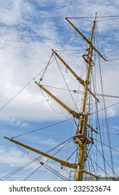 Mast against the background of the cloudy blue sky