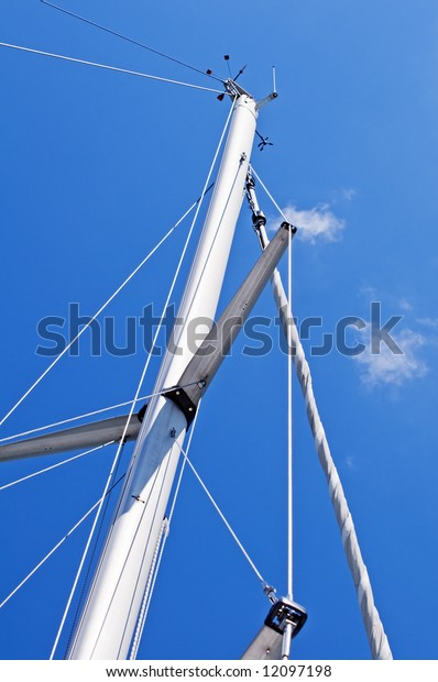 Mast of a sailboat against a blue sky