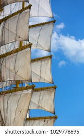 The mast of a sailboat with the sails against the blue sky