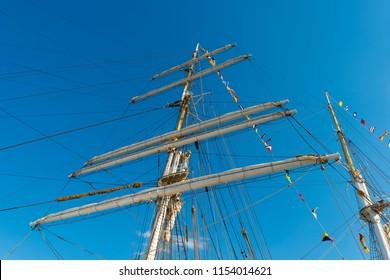 Mast of a sailing ship frigate on the blue sky