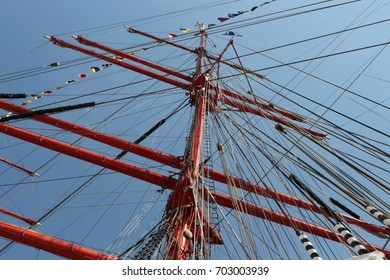 the mast of sailing ship with rigging blue sky