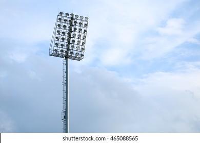 Mast with spotlights illuminate on stadium and blue sky background