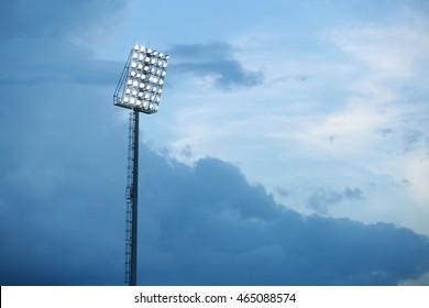 Mast with spotlights illuminate on stadium and raincloud background