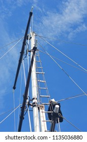 The mast of a yacht, complete with rigging, is seen against a blue sky. There are a few faint white clouds. A rope ladder stretches to the top of the mast.