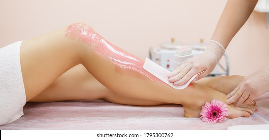 A master applies pink depilatory wax to a young woman's leg for hair removal. Depilation with wax. Beauty concept. Place for text. Selective focus.