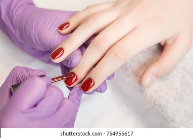 Master applies varnish drawing on nails gel in manicure salon.