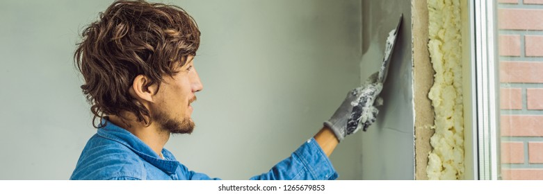 master is applying white putty on a wall and smearing by putty knife in a room of renovating house in daytime BANNER, LONG FORMAT