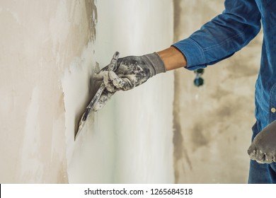 master is applying white putty on a wall and smearing by putty knife in a room of renovating house in daytime