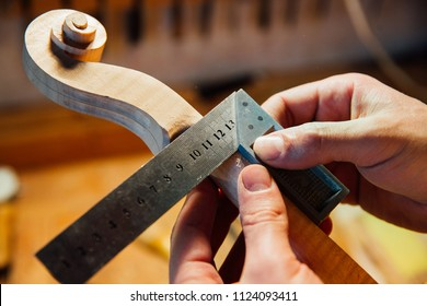 Master artisan luthier working on creation of a violin scroll. detailed work on wood with tools. Men's hands Measures the thickness of the scroll with meter . on the background of a workshop
