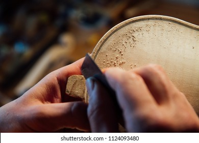 Master artisan luthier working on the creation of violin. detailed work with blade in the artist's hand. the working process. wood shavings and dust from the body. active dynamic workflow.