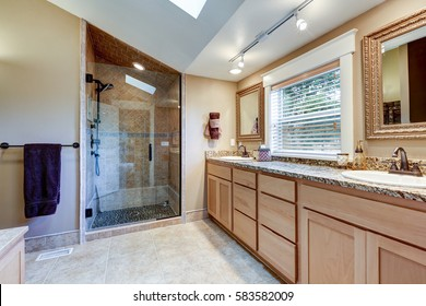 Master bathroom interior with large double sink vanity cabinet topped with granite countertop, glass walk-in shower and vaulted ceiling with skylight. Northwest, USA