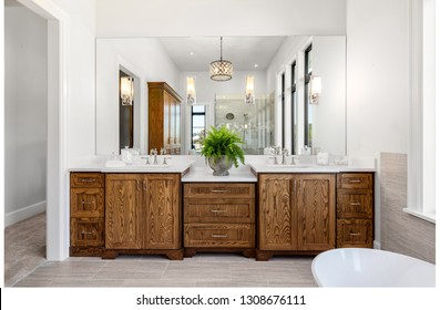 Master Bathroom Interior in New Luxury Home with Dark Hardwood Cabinets, Freestanding Bathtub, and Shower visible in Mirror Reflection