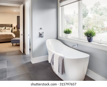 master bathroom interior in new luxury home: bathtub with view of master bedroom. includes tile floor, bathtub, faucet, window, and bed and stand in master bedroom